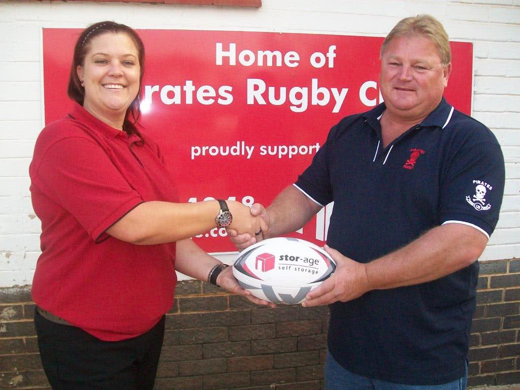 Brenda Grove hands rugby balls to Barry Miller from the Pirates Rugby Club